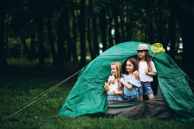 hermanos disfrutando de la experiencia de acampar en un ideal camping para ir con niños